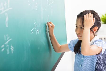 school girl doing math problems on the chalkboard
