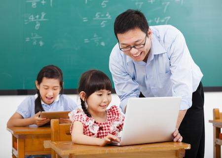 maestra ense�ando: profesor que ense�a a la computadora con los ni�os en el aula