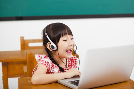happy little girl learning computer in classroom