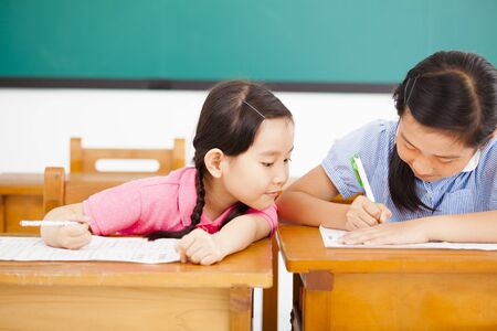 cheat: little girl student trying to cheat at test in class