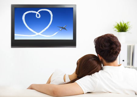 pareja viendo television: joven pareja viendo el programa de televisión en el salón