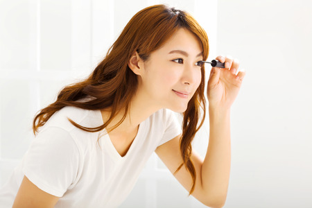 lifestyle woman: young beautiful Applying mascara in bedroom Stock Photo