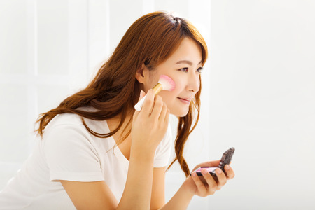 young beautiful woman with Makeup Brush Stock Photo