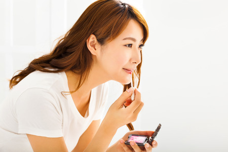 fashion make up: young woman applying lips makeup with cosmetic brush
