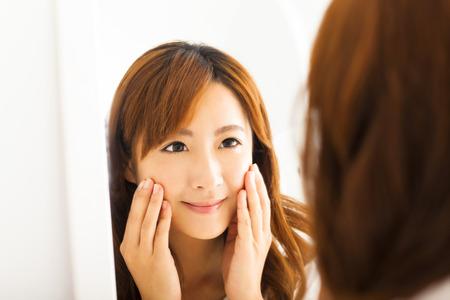 Usmívající se mladá žena hledá zrcadlo v ložnici Reklamní fotografie
