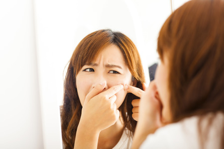 squeezing: Young  woman with pimple on her face