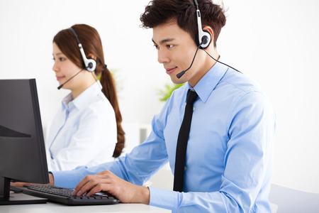 sales agent: businessman and woman with headset working in office Stock Photo