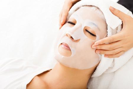 tratamientos corporales: joven con la máscara facial en el spa Foto de archivo