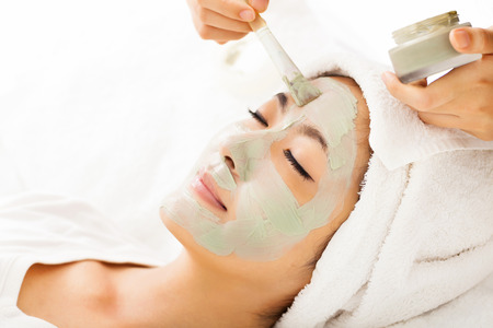 spa treatment: Young beautiful woman with clay facial mask