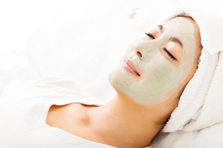 masaje facial: Mujer hermosa joven con m�scara facial de arcilla Foto de archivo