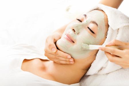 粘土の顔のマスクを持つ若い美しい女性