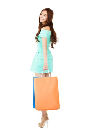 woman back view: young woman with shopping bags isolated on white