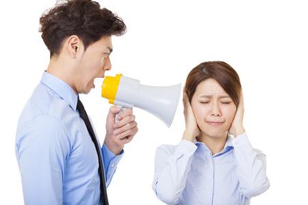 businessman using a megaphone: Businessman using megaphone to scream at businesswoman