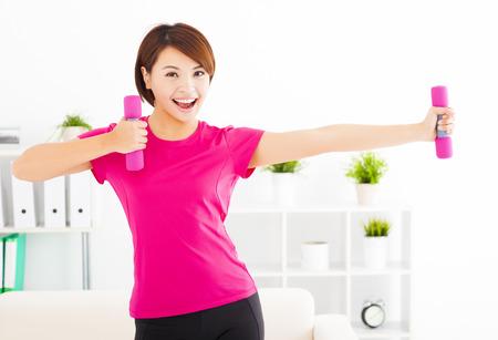 gelukkige jonge vrouw te oefenen met halters in de woonkamer Stockfoto