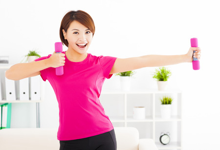 girl in sportswear: happy young woman exercising with dumbbells in living room Stock Photo
