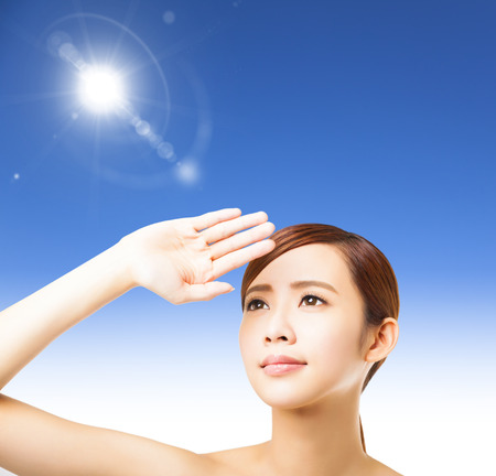 sunblock: young woman face with sunlight background