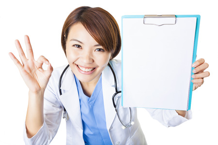 young woman doctor showing  blank clipboard with ok gesture photo