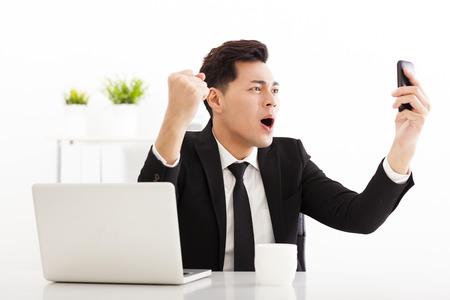 hombre de negocios feliz mirando el teléfono inteligente en la oficina