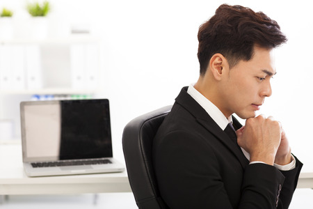 Young business man thinking in the  office photo