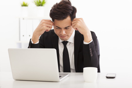 upset man: stressed business man in the office Stock Photo