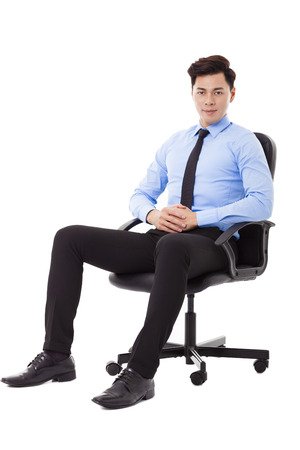 joyful businessman: Young businessman sitting in a chair isolated
