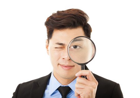 Businessman looking through magnifying glass photo