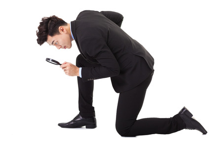 Businessman looking through magnifying glass for searching photo