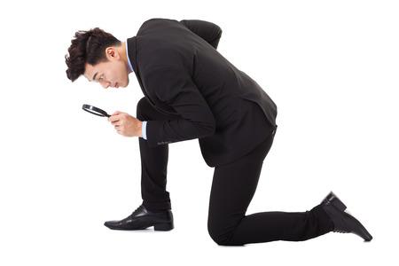 Podnikatel dívá skrz zvětšovací sklo pro vyhledávání