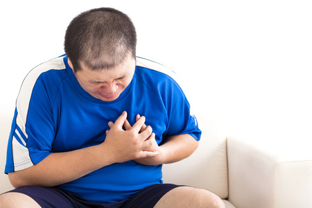fat: young fat man getting heart attack Stock Photo