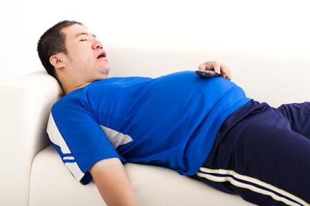 sedentario: hombre gordo dormir en el sofá y que sostiene el control remoto de la televisión Foto de archivo