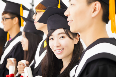 gorros de graduacion: hermosa graduado de la universidad femenina asiática en la graduación con sus compañeros Foto de archivo