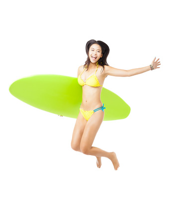 happy young Woman  holding surfboard and jumping photo