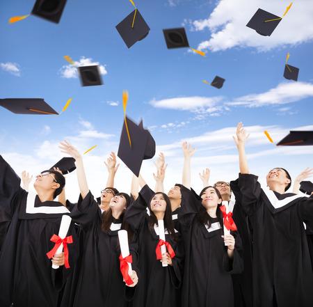 gorros de graduacion: estudiantes felices que lanzan tapas de graduación en el aire