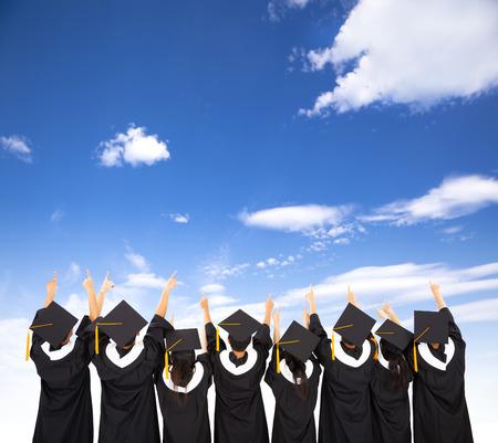toga y birrete: Vista trasera de estudiantes que celebra la graduaci�n Foto de archivo