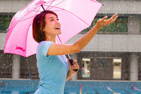 Beautiful young woman under pink umbrella