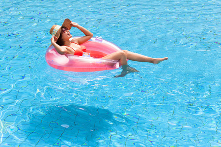 スイミング プールでリラックスした幸せの若い女性