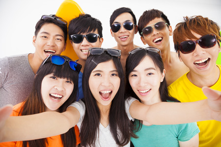 happy asian people: group of smiling friends with camera  taking selfie