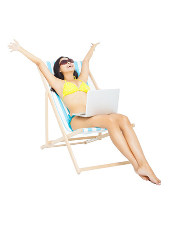 sunbed: young woman in bikini sitting with laptop
