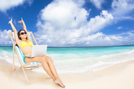 strandstoel: gelukkige vrouw met laptop op het tropische strand Stockfoto