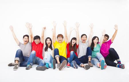 manos levantadas: Grupo de jóvenes felices sentados juntos contra la pared blanca Foto de archivo