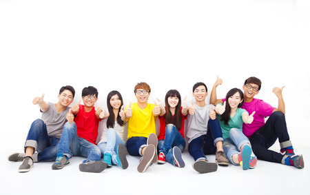 Happy young group sitting together with thumb up