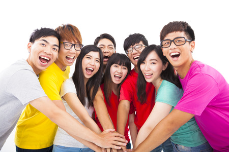 Group of young people with hands together Stock Photo