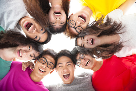 riÃ â  on: Grupo de estudiante joven feliz con los brazos alrededor de los hombros de los demás Foto de archivo