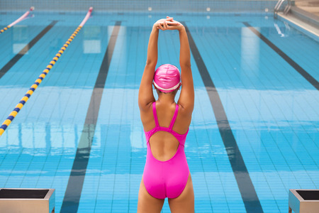 rear: Young sportswoman stretching and preparing to swimming
