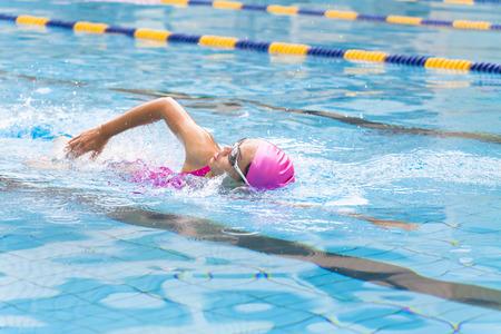 若い女性はプールで泳いでください。