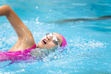 unga kvinnor simmar i poolen Stockfoto