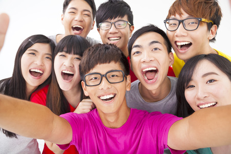 asian youth: group of smiling friends with camera  taking self photo Stock Photo