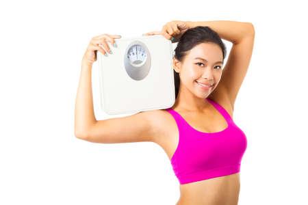 dieta sana: Mujer joven que sostiene la escala de peso