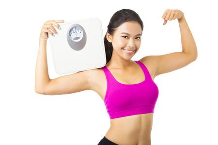 fitness: Mujer joven que sostiene la escala de peso