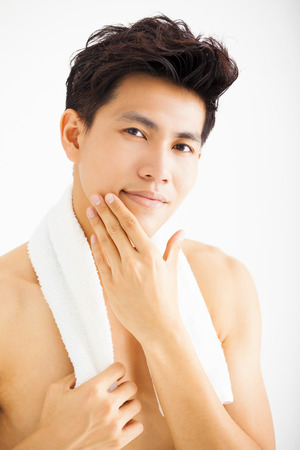 grooming: Young  man touching his smooth face after shaving Stock Photo